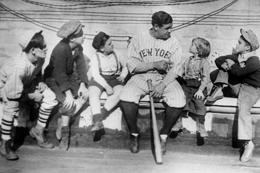 Babe Ruth sitting on a bench with kids