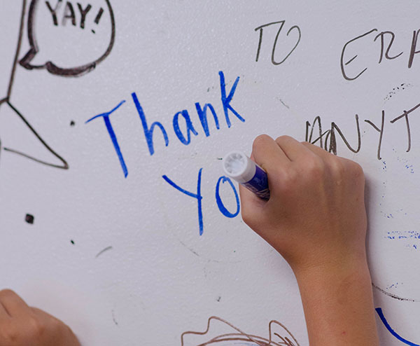 detail photo of a child writing 'thank you' on a ZURB whiteboard wall